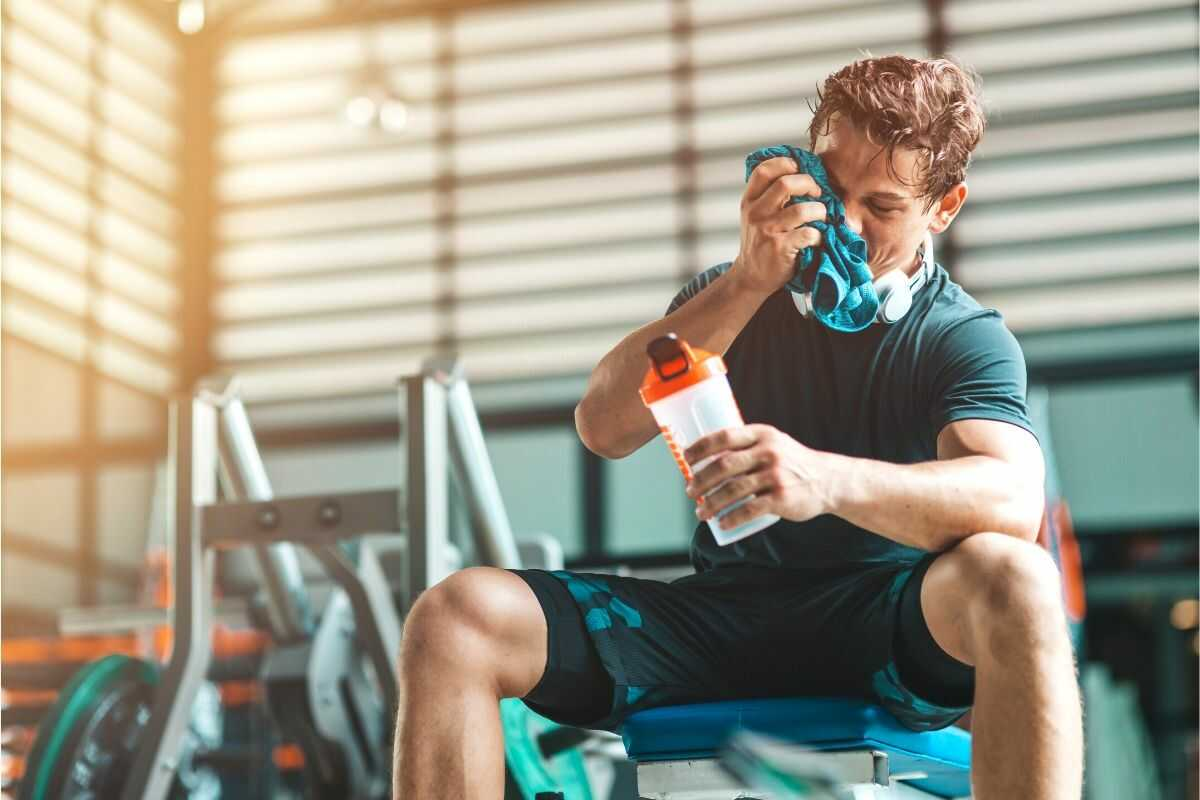uomo che beve un drink intra-workout in palestra