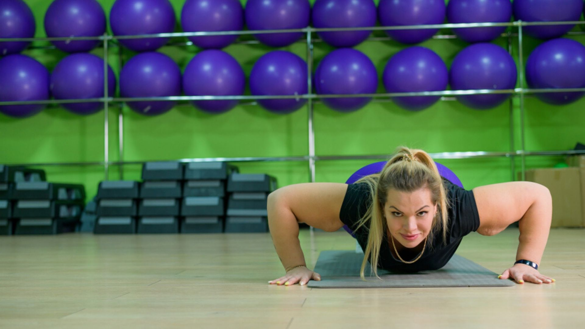 overweight woman does push ups in the gym